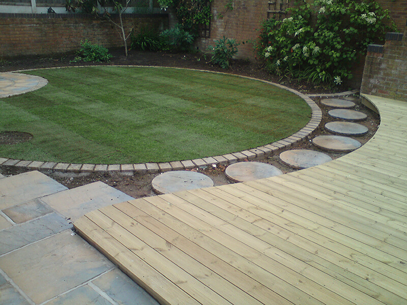 Curved landscape with deck and grass area